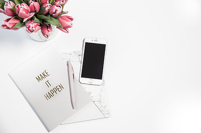 White desktop with smartphone, make it happen journal and vase full of pink tulips