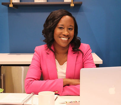 Smiling professional woman wearing a pink blazer, sitting at a desk with a laptop, coffee mug and notebook