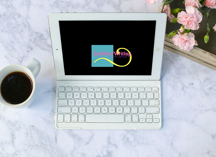 White laptop on marble desk with a cup of black coffee and a wooden bin full of pink carnation flowers
