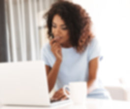 African American woman sitting at laptop with coffe mug