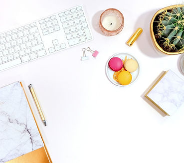White desktop with white keyboard, small white plate of colorful macaroons, white candle in a pink glass, gold lipstick, white and gold planter holding a cactus, white and pink binder clips, notepads and gold pen