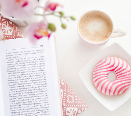 White desktop with coffee mug, book and pink and white donut and orchid