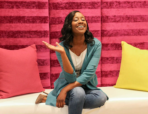 Smiling African American woman in blue jeans, blue shirt and white tea shirt sitting on white bench against a pink wall with pink and yellow pillows