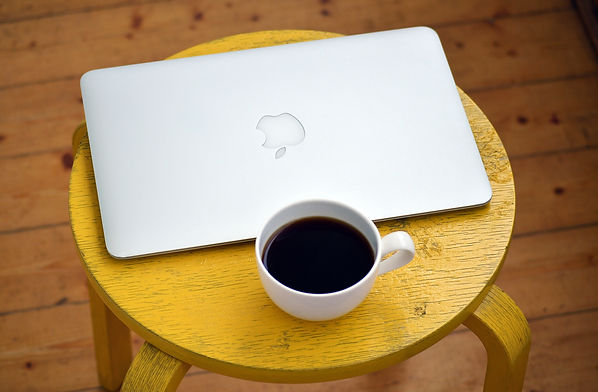 Apple laptop and white coffee mug full of black coffee on yellow wooden stool