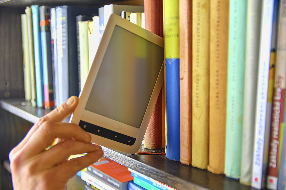 Library bookshelf filled with colorful old books and a hand pulling an e-reader out of the bookshelf
