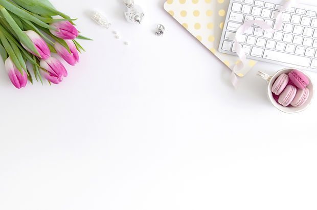 White office desktop with purple tulips, pearls, silver bird, gold and white polka dot mouse pad, white keyboard, white ribbon, and white coffee mug full of pink macaroons