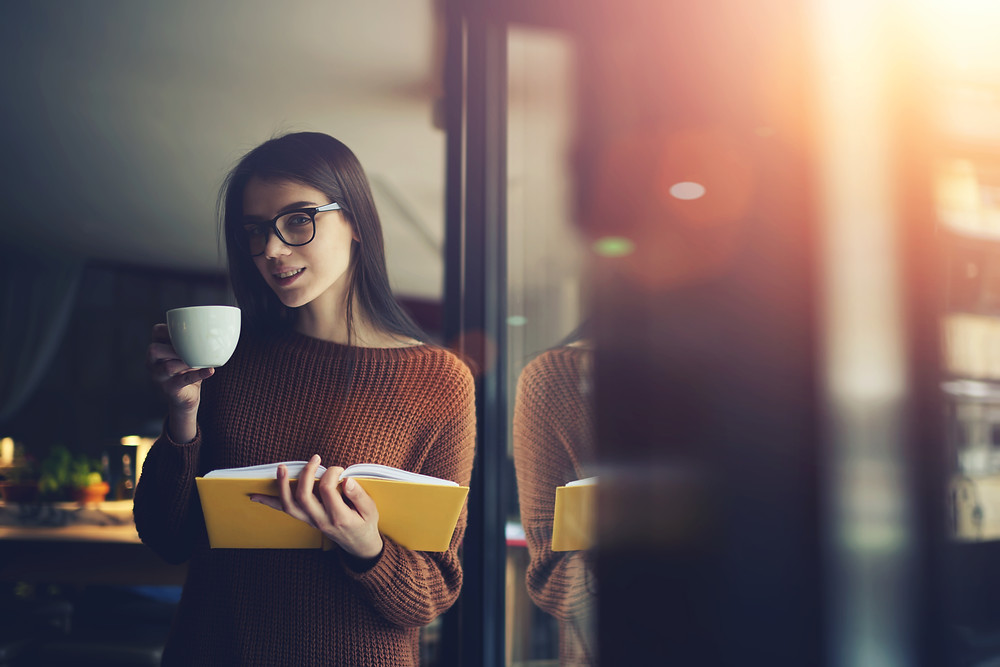Woman wearing glasses drinking coffee reading a yellow book standing next to a window