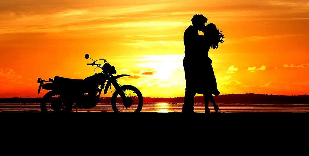 casal apaixonado e moto ao por do sol