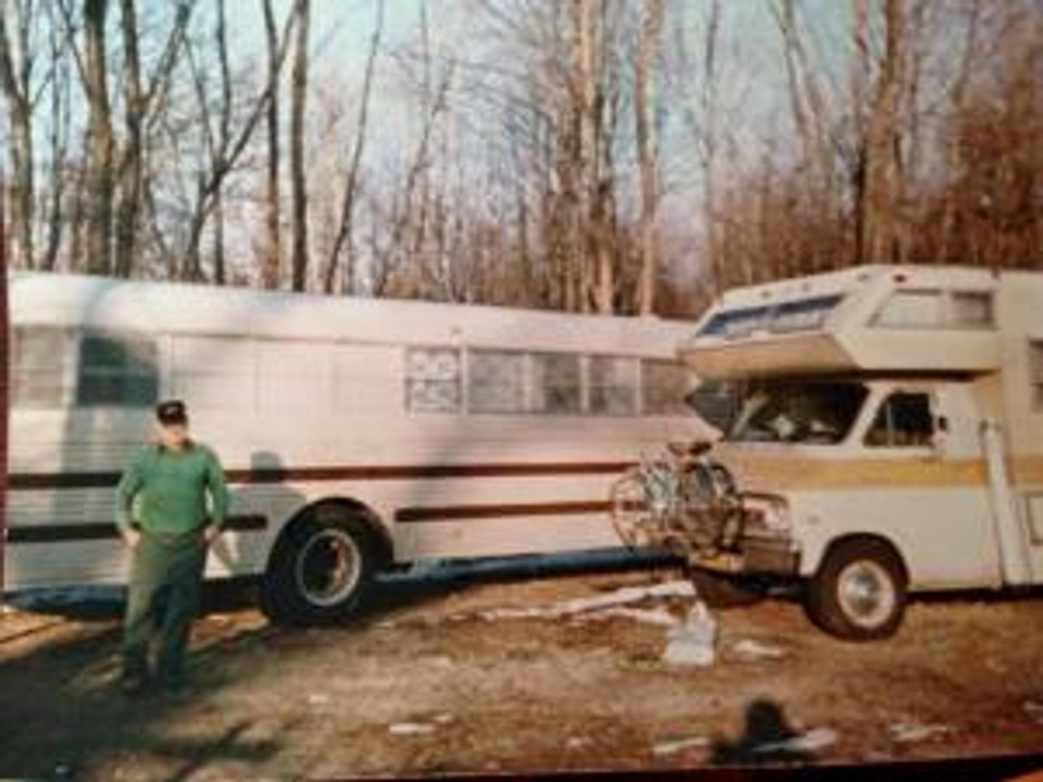 Grandpa Brown with his retirement house. An old school bus, he decked out in his free time.