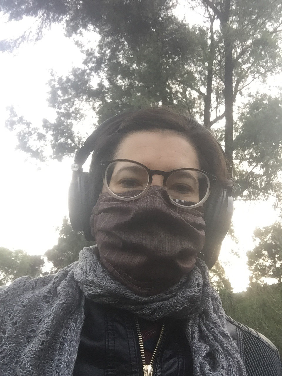A woman wearing glasses, headphones and a pandemic mask poses in front of a tree