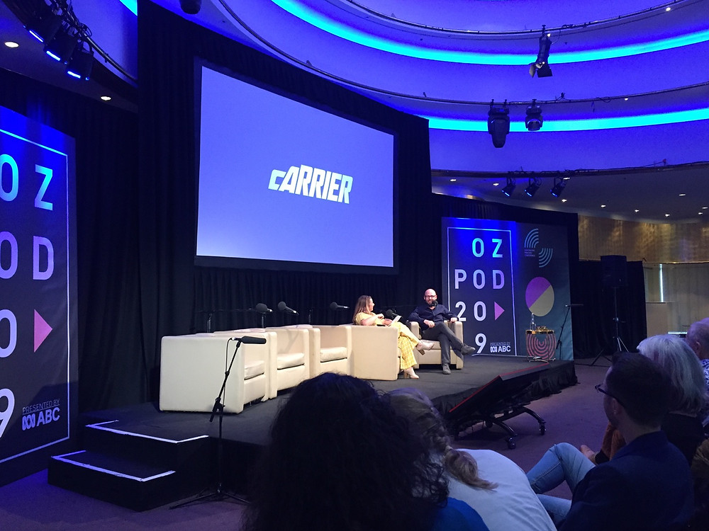 """A woman and a man at a conference sitting in front of a large screen that reads """"carrier"""""""