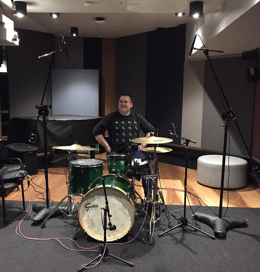 Claire sitting at a drum set, smiling. The drum set is in a recording studio surrounded by multiple microphones.