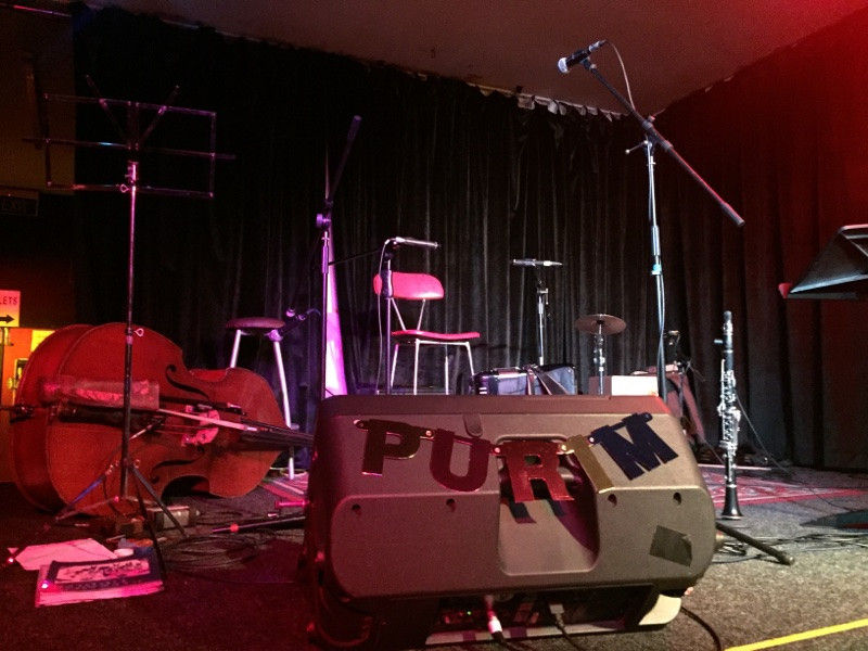 A stage that has been set up but is empty of people. A double bass is in the background. The foreground contains a speaker with a sparkly sign that says 'Purim'.