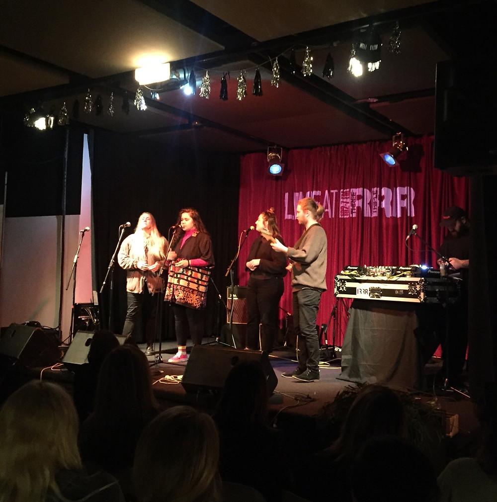 Bumpy performing at RRR. Three women singing, one man playing electric guitar.