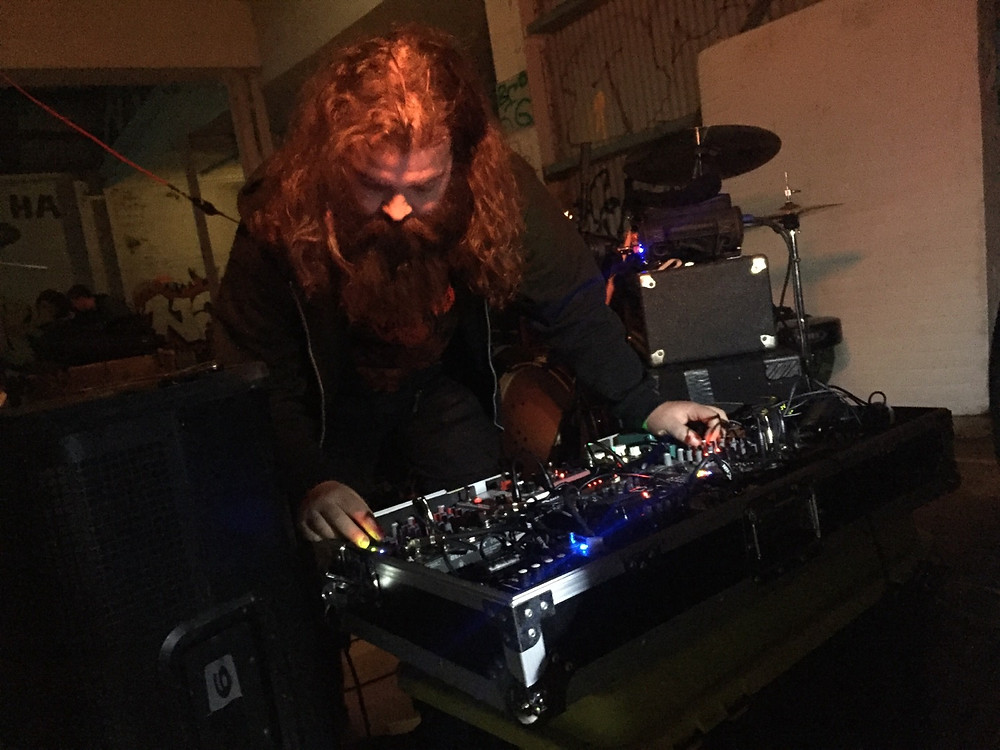 A man dressed in punk clothing leans over a large array of effects pedals. He is located in a decrepit warehouse, surrounded by music equipment such as a drum kit.