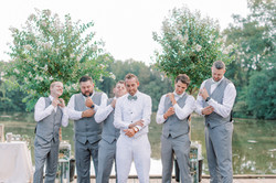 groomsmen on lake, groom unique look, groom in all white, groomsmen in grey