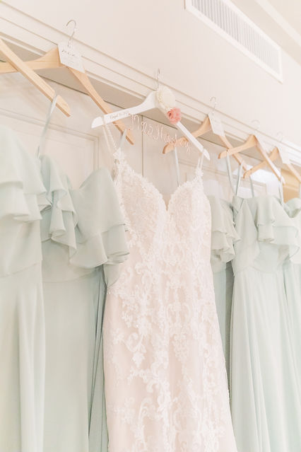 bridesmaids dresses from Kennedy Blue and bridal dress from wren bridal hanging in hotel weyanoke suite in farmville VA