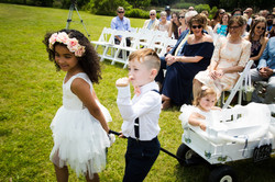 flower girls and ring bearer carrying wagon with flower crown at outdoor maryland wedding venue