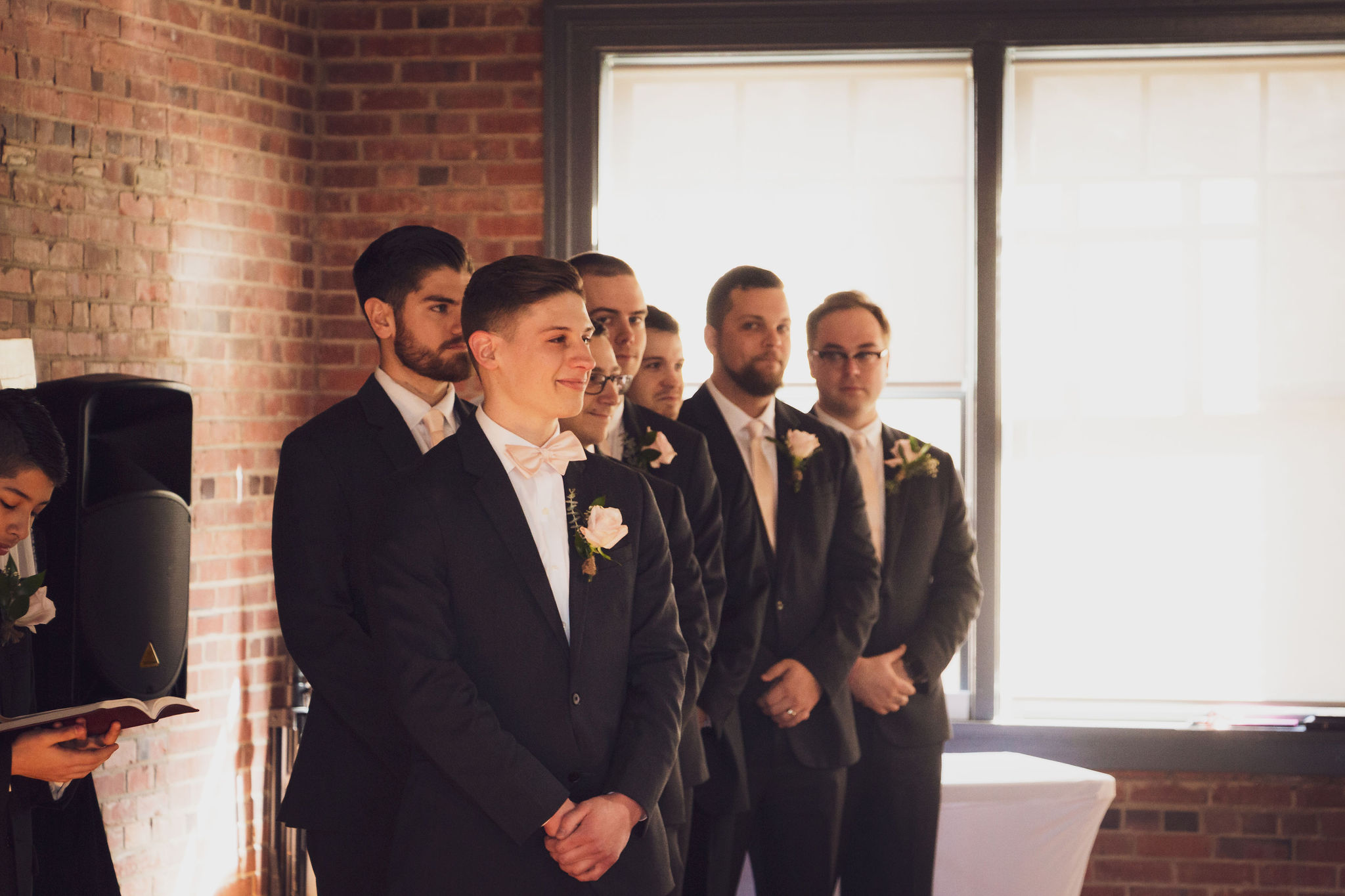 groom on wedding day, groom at alter with pink rose and 6 groomsmen brick venue