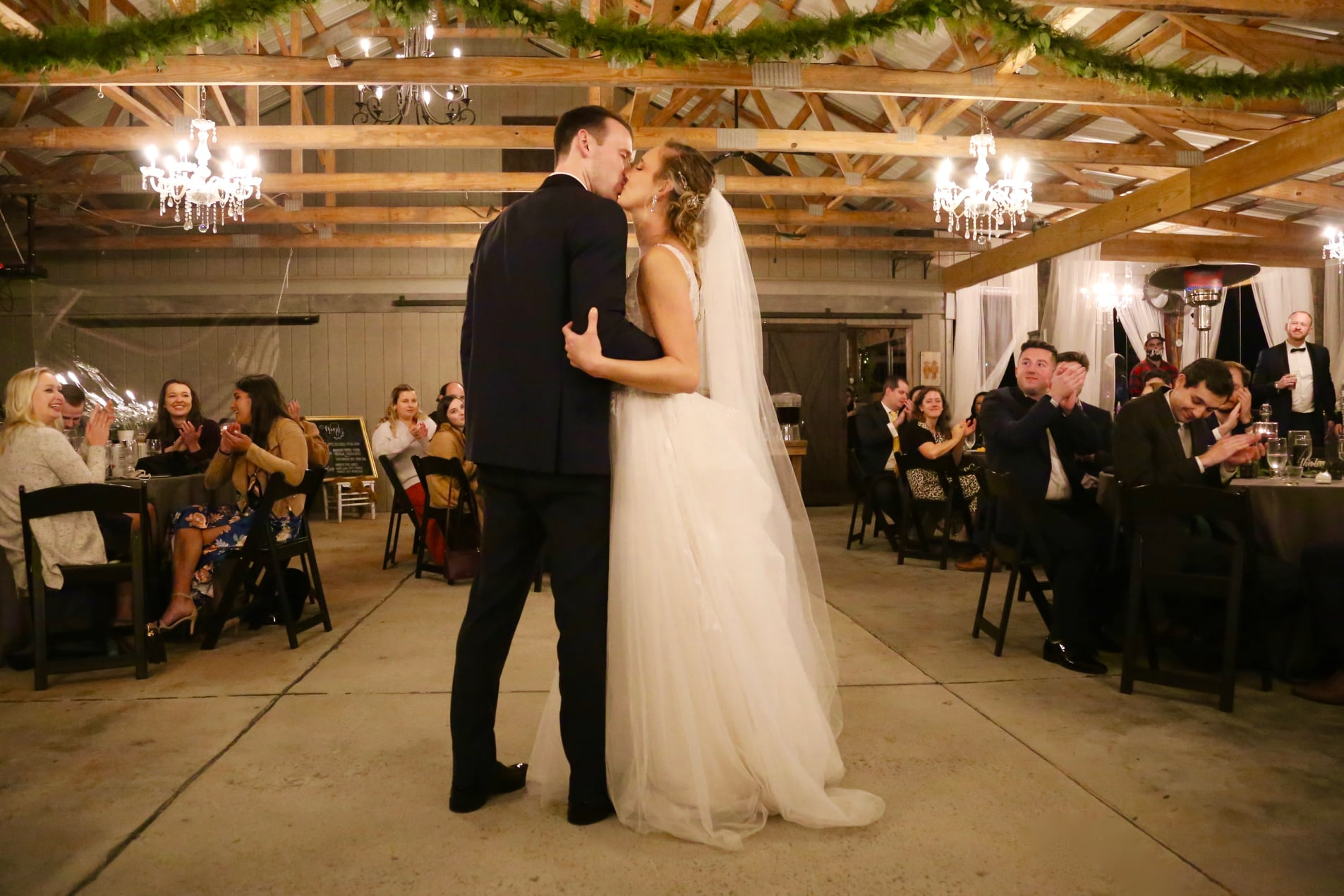chandelier event venue in raleigh for the perfect wedding day kiss between bride and groom