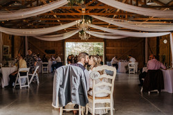 groom suit jacket on back of sweetheart table chair during barn wedding reception with white drapes