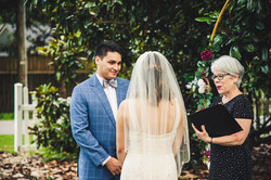 bride and groom with officiant at outdoor wedding ceremony