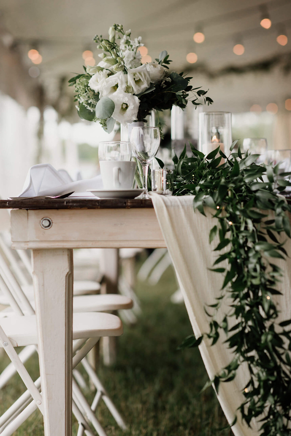 farmhouse table with gauze runner and greenery garland