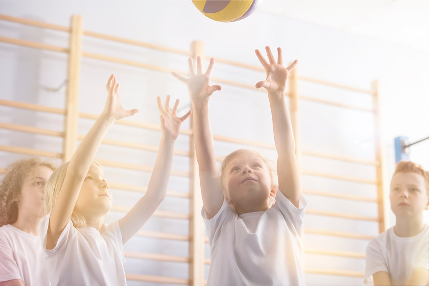 Canva - Active children playing volleyba
