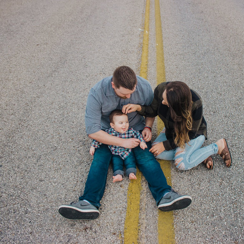 mom and dad holding child sitting on the road in corpus christi texas