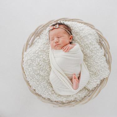 Newborn baby laying in basket