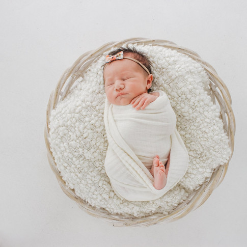 Newborn baby laying in basket
