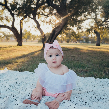 baby girl sitting on a white blanket in a field in corpus christi texas