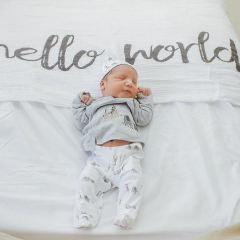 newborn baby laying on a white blanket