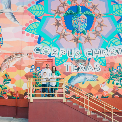 family standing in front a corpus christi mural in corpus christi texas
