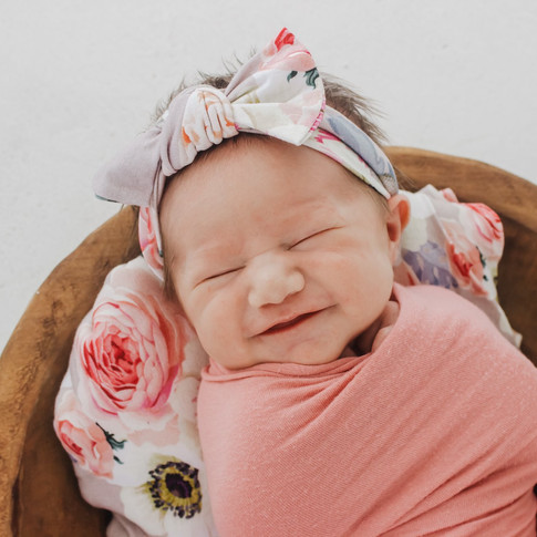 newborn baby laying in bowl smiling