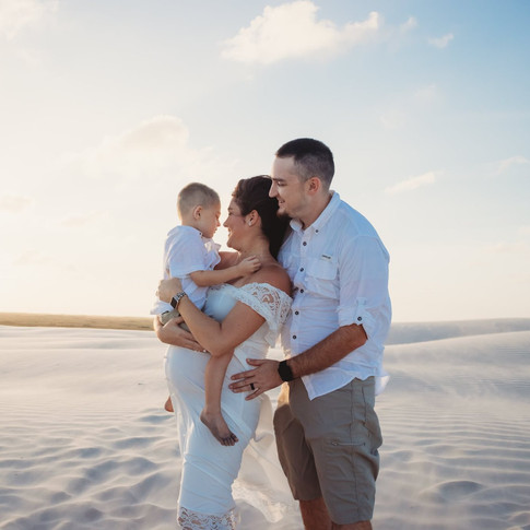 pregnant woman holding son with husband on beach in corpus christi texas