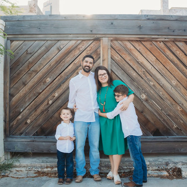 Family standing in front of a wood door in corpus christi texas