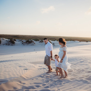 Pregnant woman and husband holding hands with their young son on beach in corpus christi texas