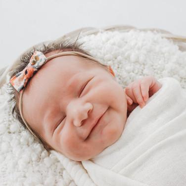 Newborn baby smiling in basket