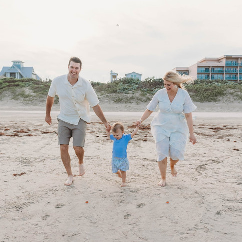 mom and dad hold hands with child on the corpus christi beach