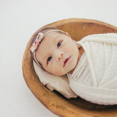 newborn baby with eyes open laying in bowl