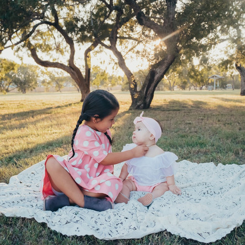 young girl and her little sister sitting on a white blanket in a field in corpus christi texas