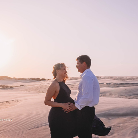 pregnant woman with husband on beach in corpus christi texas