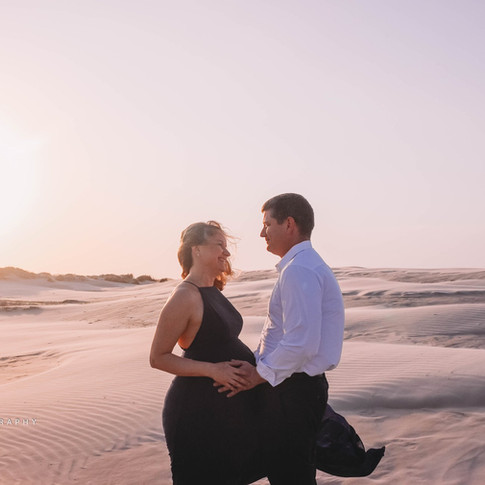 pregnant woman with husband on beach in corpus christi texas