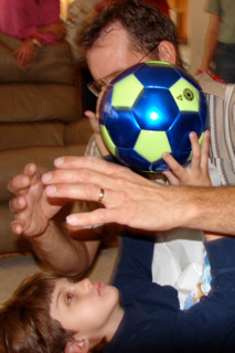 10-year old Dylan is lying on his back holding a new soccer ball. Roy, Dylan's Dad, is leaning over him signing ball as Dylan looks intently on. With a hand on each side of the ball, Dylan's hands perfectly match his father's hands.