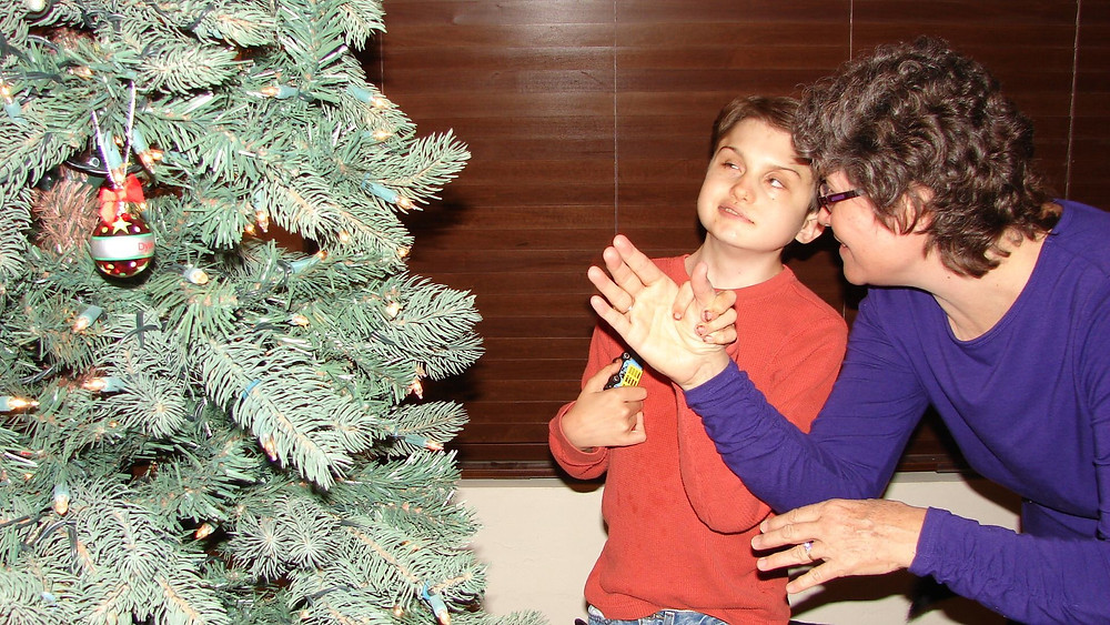 Dylan's hand is on Kim's as they finish co-signing Christmas tree. Both are smiling as Dylan looks to the tree with a shiny round Dylan ornament on it.