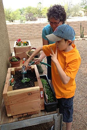 Dylan, a young man with CHARGE syndrome, is signing water as he sprays water on his plant in the redwood plantar box he made.