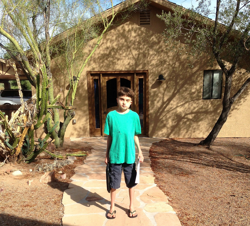 Dylan is standing in front of his School-Home building, holding his iPad and a co-drawn story.