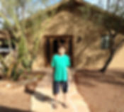 Dylan is standing on a flagstone walk in front of his School-Home at Redtail NC