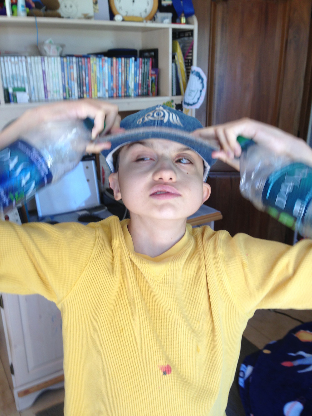 Dylan, holding a water bottle in each hand is pulling his hat onto his head.  His look says, I am ready to go.
